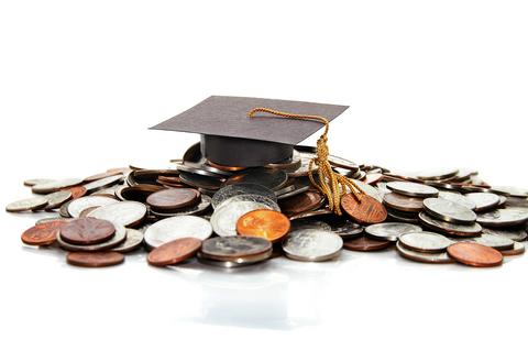 Examenshatt på hög av mynt